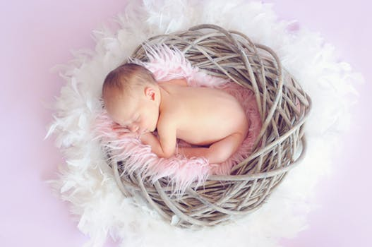 Example of Easter themed baby photography Glasgow with a baby laying on a feathery blanket inside an artificial nest