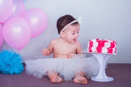Baby in tutu sitting next to a large pink frosted cake for professional baby photography Glasgow